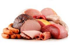 Köttprodukter inklusive skinka och korvar på vit arkivfoto