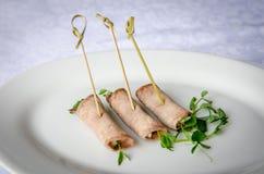 Köttrullar på steknålar på den vita plattan olika mellanmål Arkivfoto