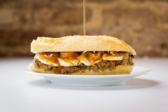 Köttsmörgås med söt lök- och getost Arkivfoton