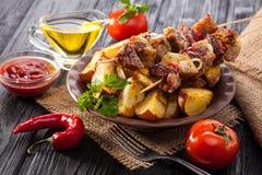 Köttsteknål med örter med lökar, bakade potatisar, tomater och gräsplaner Arkivfoton