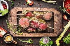 Köttsteknålar med gröna örter täcker med en skorpa för gallret eller matlagning, förberedelse på mörk lantlig träbakgrund fotografering för bildbyråer