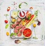 Köttsteknålar med nya bitande grönsaker och smaktillsats på emaljplattan Köttsteknålar för gallret eller matlagning, förberedelse arkivfoto