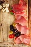 Köttuppläggningsfat av Cured kött och oliv på gammalt träbräde Royaltyfria Foton
