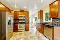 Küche mit schwarzen Granitoberteilen und hölzernen Kabinetten Stockbild