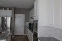 Küche mit weißen Kabinetten Stockfotografie
