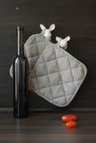 Küche noch mit einer Flasche, Tomaten und keramischen Figürchen Stockfotografie