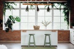 Küchen-Innenraum mit Insel, Wanne, Kabinetten und Massivholzböden stockfotos
