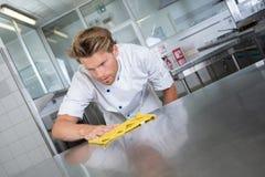 Küchenarbeitskraft, die Station abwischt stockfoto
