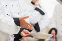Küchenchef, der Klasse eine Schüssel zeigt Stockfotografie