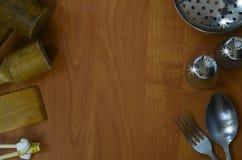 Küchengeräte auf hölzernem Hintergrund Stockbilder