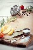 Küchengeräte, -gewürze und -kräuter, die Fische kochen Stockfotografie