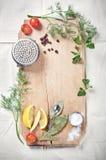 Küchengeräte, -gewürze und -kräuter für das Kochen von Fischen Lizenzfreie Stockfotografie