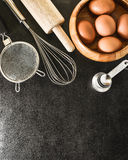 Küchengeräte und Backenbestandteile: Ei und Mehl auf schwarzem Hintergrund Lizenzfreie Stockfotografie