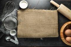 Küchengeräte und Backenbestandteile: Ei und Mehl auf schwarzem Hintergrund Stockfotografie