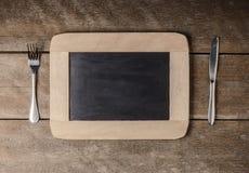 Küchengeschirr auf einer Tafel mit einer blauen karierten Serviette Lizenzfreie Stockbilder