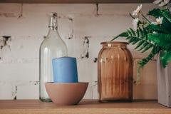 Kücheninnenraum: Flasche, Glas, Kerze und Blumen in einem Vase im Regal Gemütlicher Hauptinnenraum stockbild