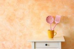 Küchenkochgeräte. Plastikspachteln in der gelben Schale gegen rustikale Terrakottawand. Lizenzfreie Stockfotos