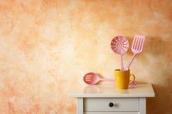 Küchenkochgeräte. Plastikspachteln in der gelben Schale gegen rustikale Terrakottawand. Lizenzfreie Stockfotografie