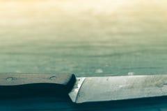 Küchenmesser gesessen auf einem hölzernen Hintergrund Lizenzfreies Stockbild