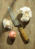 Küchenmesser mit Knoblauch und Schalotte. Stockbild