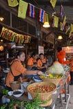 Küchenpersonal, das hilft, traditionelles Lebensmittel an sich hin- und herbewegendem Markt in Bangkok, Thailand zuzubereiten lizenzfreies stockbild