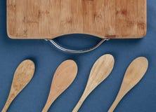 Küchenschneidebrett und ein hölzerner Löffel auf einem Blau Stockbilder