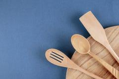 Küchenschneidebrett und ein hölzerner Löffel auf einem Blau Stockbild