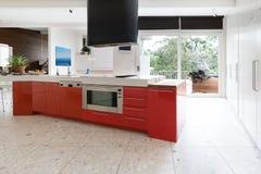 Küchenschränke des orange Rotes in der Insel setzen in modernem Luxus-Aus auf die Bank lizenzfreie stockfotografie