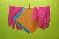 Küchenschwämme und Gummihandschuhe, die am Seil hängen stockbild