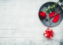 Küchentischbesteck auf Platte mit Geschenk und Rotrose Glücklicher Valentinsgrußtag lizenzfreies stockbild