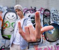 Kühl-Schauen des jungen Mannes vor Graffiti lizenzfreie stockfotos