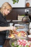 Kühle blonde Frau bereitet gebratene Kartoffeln zu Stockfotos