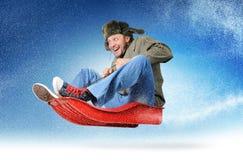 Kühle Fliege des jungen Mannes auf einem Schlitten im Schnee
