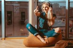 Kühle junge blonde Frau, die gute Musik in den Kopfhörern hört und Lizenzfreie Stockfotos