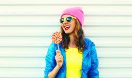 Kühle lachende Frau der Porträtmode recht mit Lutscher in der bunten Kleidung über dem weißen Hintergrund, der einen rosa Hut trä Stockfoto