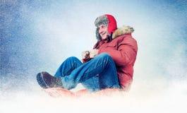 Kühle Mannfliege auf einem Schlitten im Schnee, Konzeptwinterspaß Stockbild