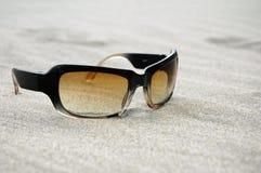 Kühle Sonnenbrillen auf einem sandigen Strand Lizenzfreie Stockfotos