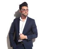 Kühle tragende Sonnenbrille des Geschäftsmannes, seine Jacke ziehend Stockbild