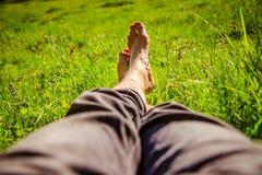 Kühlen im grünen Gras: Beine eines jungen Mannes, entspannend, Sommerzeit lizenzfreie stockbilder