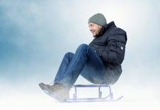 Kühlen Sie bärtigen Mann auf einem Schlitten im Schnee ab Lizenzfreie Stockbilder