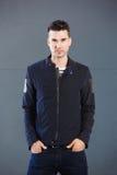 Kühlen Sie das junge männliche Mode-Modell ab, das gegen grauen Hintergrund steht Stockfoto