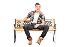 Kühlen Sie das junge männliche Modell ab, das auf einer Bank sitzt Stockbilder