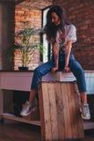Kühlen Sie das moderne Mädchen ab, das eine weiße Spitze und Jeans sitzen auf einer Tabelle im Studio mit Dachbodeninnenraum träg Stockbild