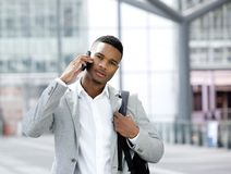 Kühlen Sie den jungen Mann mit Tasche sprechend am Handy ab Stockfoto