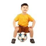 Kühlen Sie den kleinen Jungen ab, der auf einer Fußballkugel sitzt stockbilder