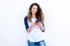 Kühlen Sie die junge Frau ab, die mit Mobil-Telefon gegen weißen Hintergrund lächelt lizenzfreies stockbild