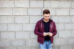 Kühlen Sie jungen Mann mit dem Bart ab, der das Mobile schaut Stockbilder