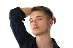 Kühler überzeugter blonder junger Mann mit blauem Hemd, Hand über Kopf Stockfoto