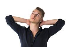 Kühler überzeugter blonder junger Mann mit den Händen hinter Kopf Stockbilder