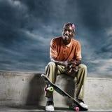 Kühler afrikanischer Skateboarder, der sich zum Rest hinsetzt Lizenzfreie Stockfotografie